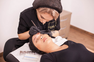 Woman cosmetologist doing an eyebrow tattoo removal procedure on a female client. Skin treatment. Modern techology. Beauty salon.