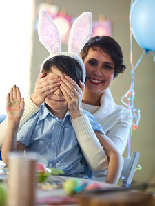 Woman covering her son eyes on his birthday