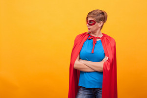 Woman dressed like superhores standing proudly and looking away over yellow background. Woman super powers. Red cape. red mask