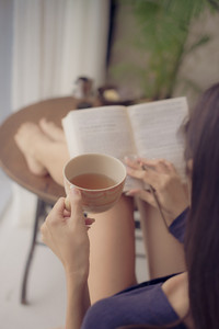 Woman drinking tea while reading a book at home, rear view