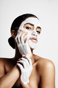 woman during facial treatment. white cream mask on her face and hands