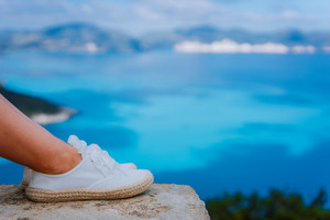 Woman feet wearing white espadrilles in front of beautiful seascape. Funny and happy fashion young woman on vacation. Chill out girl at viewpoint. Holidays Weekend travel