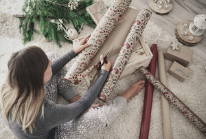 Woman flooring and cutting wrapping paper