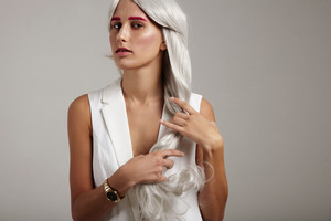 woman gently touches her grey hair