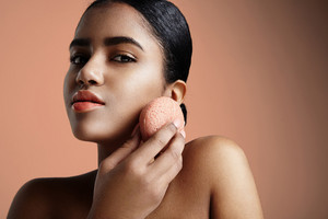 woman has a treatment with a pink konjac facial sponge