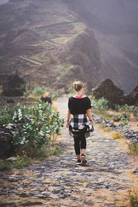Woman hiker on the picturesque coastal cobbled route. The road joins the towns of Cruzinha, Fontainhas and continues on the way to Ponta do Sol. Santo Antao. Cape Verde