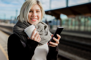 Woman Holding Coffee Cup And Mobile Phone At Train Station