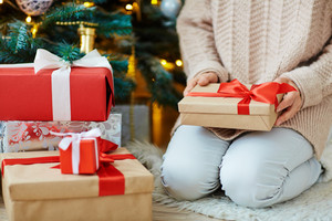 Woman holding packed xmas gift tied up with red ribbon