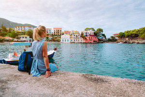 Woman in blue dress sitting on the pier and looking to the picturesque bay. Assos village with beautiful traditional houses on summer morning. Summer vacation Kefalonia, Greece