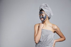 woman in grey towels with grey facial mask