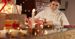 Woman in thick white cable sweater wrapping presents on the background of Christmas decorations and lights