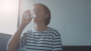 woman in top with stripes drinking water in sunny space with window