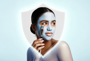 woman into shining shield put a facial mask. Skin save concept