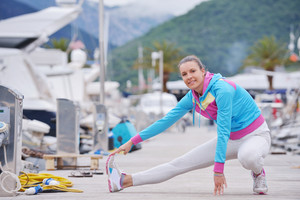 woman jogging at early morning with yacht boats in marina