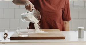 woman nakes dough in sunlight kitchen
