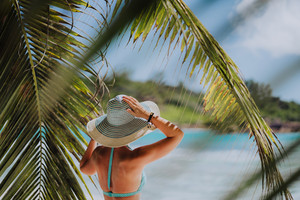 Woman on the beach in the palm trees shadow wearing blue hat. Luxury paradise recreation vacation concept