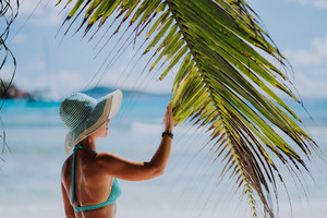 Woman on the beach touching palm tree leaf shadow wearing blue hat. Luxury paradise recreation vacation concept