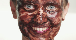 woman portrait with a chocolate facial mask on a white background