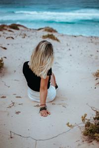Woman sitting in white sand dune admiring coastline andscape and waves of Atlantic ocean. Sao Vicente. Calhau. Praia Grande. Cape Verde