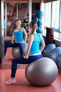 Woman sitting on the pilates ball in front of mirror in the gym