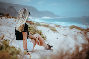 Woman sitting on white sand dune with barren vegetation admiring coastline landscape and atlantic ocean waves. Sao Vicente Cape Verde