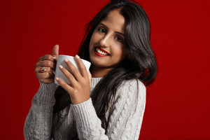 woman smiling and watching at camera. holding a white cup of tee
