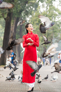 Woman standing among flying pigeons