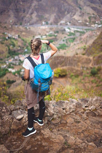 Woman tourist on cobbled path looking over picturesque village Coculi. Santo Antao, Cabo Verde