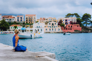 Woman tourist sitting on the pier and looking to the picturesque bay. Assos village with beautiful traditional houses on summer morning. Summer vacation Kefalonia, Greece