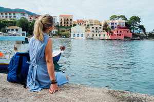 Woman tourist wearing blue dress sitting on the pier and looking to the picturesque bay. Assos village with beautiful traditional houses on summer morning. Summer vacation Kefalonia, Greece