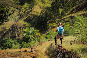 Woman tourist with blue backpack making photo of landscape in Mountains of Santo Antao island, Cabo Verde