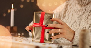 Woman unrecognizible in thick white cable sweater wrapping presents on the background of Christmas decorations and lights