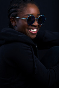 Woman Wearing Sunglasses While Smiling Over Black Background