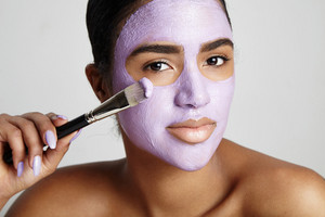 woman with a clay facial mask and brush