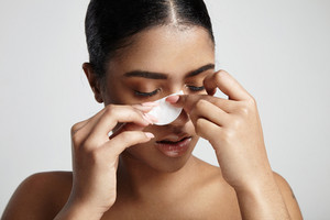 woman with a cotton pad making facial routine