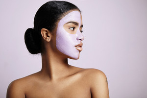 woman with a facial mask looks aside on a violet background