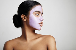 woman with a facial mask looks aside