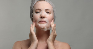 woman with a facial sheet mask on makes herself a facial a massage