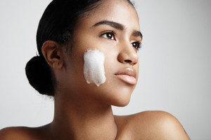 woman with a foam on a cheek. Cleansing skin concept