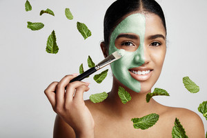 woman with a fresh green mask with avocado and mint leavs in air