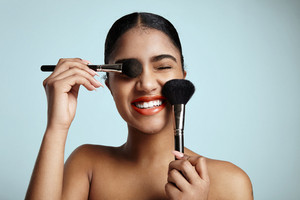woman with a two cosmetic brushes is smiling