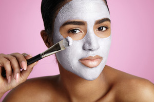 woman with a white clay facial mask and brush
