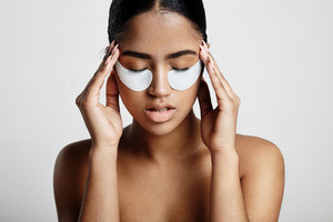 woman with an eye patches touching temples. skin stress concept