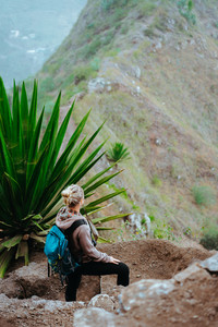 Woman with backpack on the trekking route near mountain edge looking down to valley. Santo Antao island, Cabo Verde