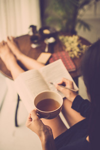 Woman with big mug of tea reading a book and making notes