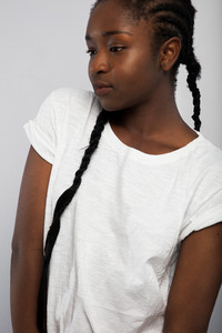 Woman With Braided Hair Looking Away Over Gray Background
