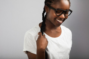 Woman With Braided Hair Wearing Eyeglasses Over Gray Background