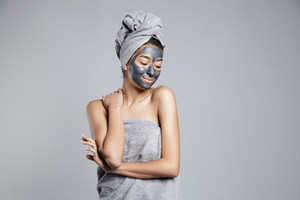 woman with clay cleansing facial mask