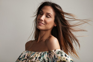 woman with closed eyes and flying hair is smiling