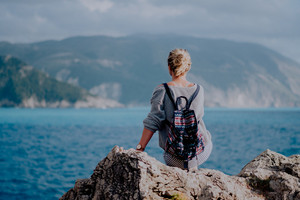 Woman with colorful backpack siting on rocky shore looking to the sea and island on the horizon. Stormy weather